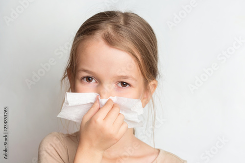 Runny nose in children. A child blows his nose in a handkerchief Fototapete