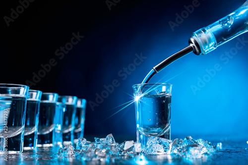 Obraz na płótnie Vodka poured into a glass lit with blue backlight.