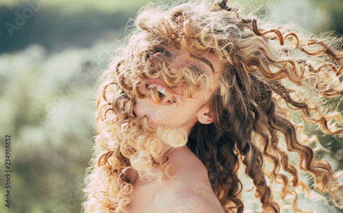 Fototapeta premium Blonde spring girl with curly beautiful hair smiling. Beauty hair Salon. Fashion haircut. Beauty girl with long and shiny curly hair. Trendy haircuts. Long healthy hair. Spring emotions.