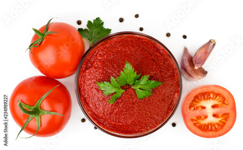 Photo Tomato paste in a glass plate, tomatoes, garlic and pepper on a white background