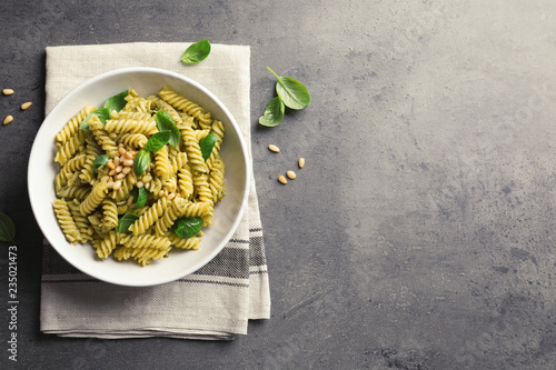 Plate of delicious basil pesto pasta on gray table, top view. Space for text