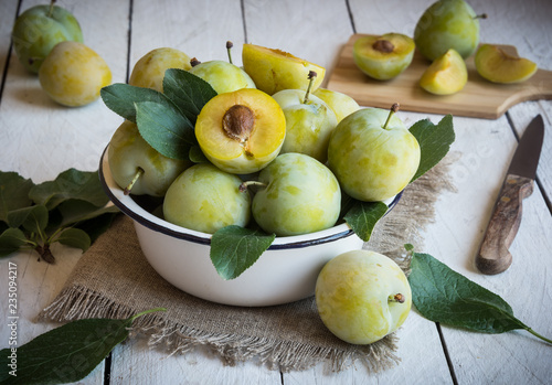 Fresh green plums in a bowl on white wooden table