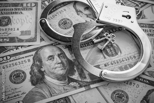 Fotografiet Pair of metal police handcuffs on USD US dollar banknotes money cash background