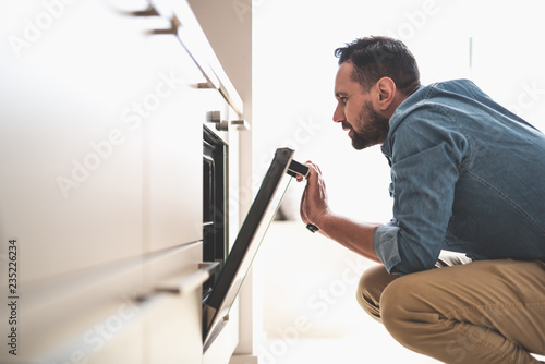 Side view portrait of handsome gentleman in denim shirt looking into oven while squatting on the floor