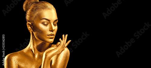 Golden skin woman portrait closeup. Sexy model girl with holiday golden shiny professional makeup. Golden metallic body