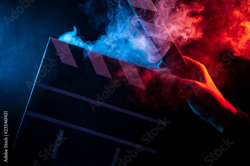 Fotografía Close-up on an open clapperboard in hand before starting shooting a film with mu