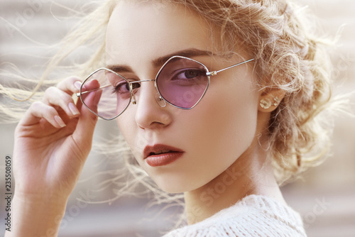 Outdoor close up portrait of young beautiful fashionable girl wearing purple sunglasses, posing in street of european city