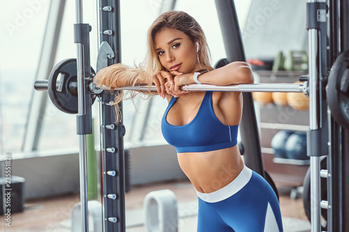 Foto Sexy girl wearing sportswear is posing next smith machine in the fitness center