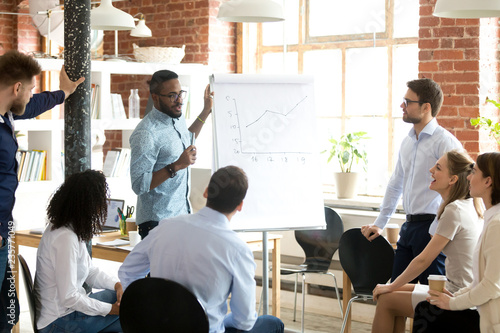 Confident smiling African American business coach speaking presentation to colleagues group at briefing, company meeting, explaining growth of sales graph, reporting about good result, motivating