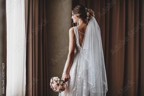 Tela Gorgeous bride in a beautiful dress. Morning newlyweds.