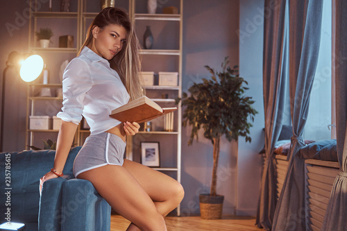 Photo A sexy girl in a translucent blouse without underwear sits on a sofa and holding a book at home, looking at a camera seductively