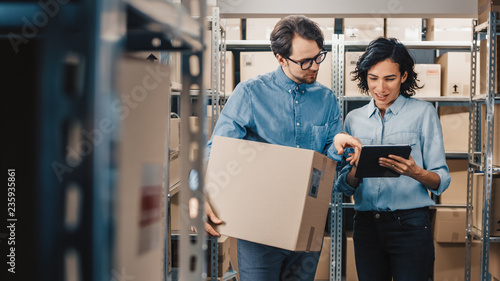 Fotografía Female Inventory Manager Shows Digital Tablet Information to a Worker Holding Cardboard Box, They Talk and Do Work