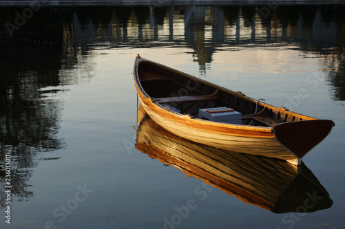 Fotografia Empty rowboat on water with reflection