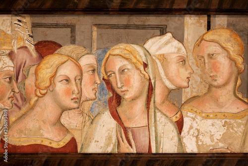 Kobiece głowy na XIV-wiecznym fresku w historycznym Palazzo del Podesta