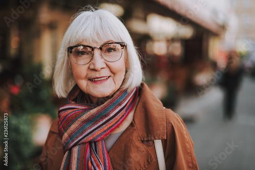 Fototapeta premium Portret elegancka stara dama patrzeje kamerę i ono uśmiecha się w żakiecie. Ulica na zamazanym tle