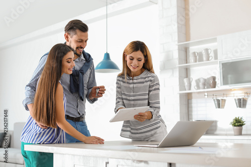 Female real estate agent working with couple, indoors
