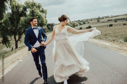 Obraz na plátne Wedding couple running on the road