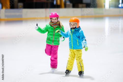 Fototapeta Child skating on indoor ice rink. Kids skate.