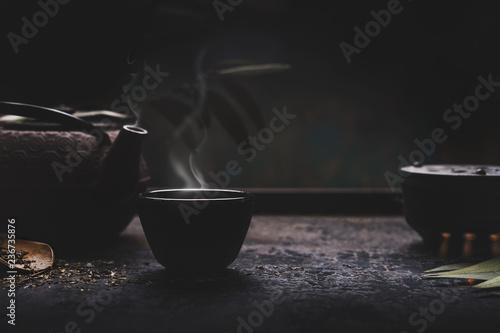Obraz na plátně Dark tea background with black iron asian teapot and mug of hot tea with steam on table