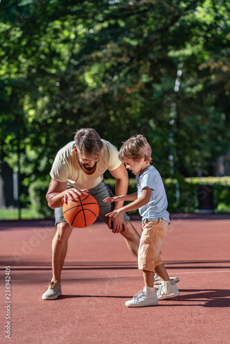 Family playing basketball in summer