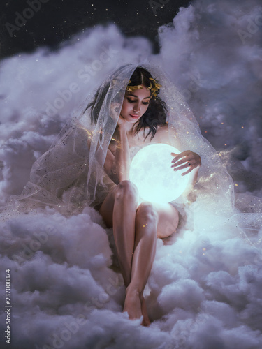 Obraz na plátně gorgeous slender sexy lady sits in the clouds and holds the moon in her hands