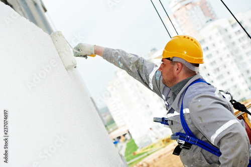 Photographie builder worker painting facade of building with roller