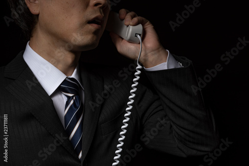 Fotografia 電話で話をするスーツの男性