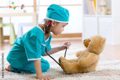 Funny child girl pretending she is a doctor in hospital