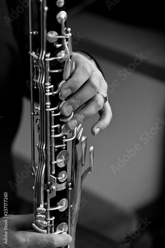 Stampa su Tela The hand of a musician playing the bass clarinet closeup in black and white