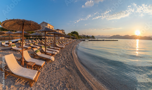 Photographie Sunbeds and umbrella on the beach at sunset time on Corfu Island, Greece