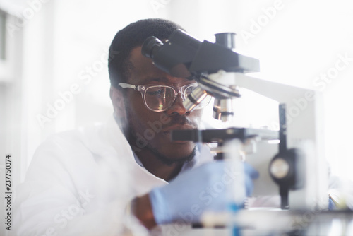 Obraz na plátně The scientist works with a microscope in a laboratory conducting experiments and formulas