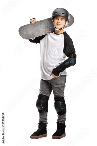Young boy posing with a skateboard on his shoulder and a helmet