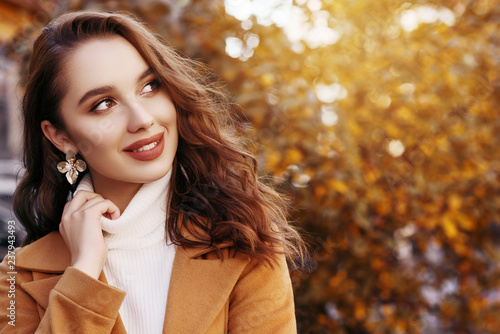 Outdoor close up portrait of young beautiful happy smiling woman with long curly hair wearing stylish coat, turtleneck, flower earrings, posing in autumn street. Copy, empty space for text