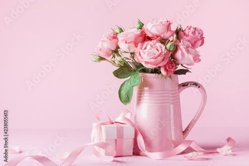Beautiful rose flowers in pink vase and gift box for Womens day or Mothers day greeting card.