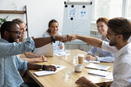 Diverse company staff girls guys sitting at desk in boardroom feel happy and satisfied celebrating success at work. Diverse colleagues fist bumping greeting each other express friendship and respect