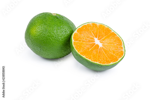 Half and whole green tangerine on a white background