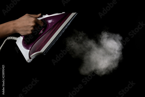 Stampa su Tela The girl lets out steam from the lilac iron on a black background
