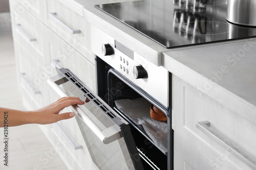 Young woman opening electric oven in kitchen, closeup