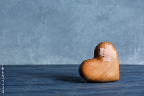 Fototapeta Wooden heart with adhesive plasters on table. Space for text