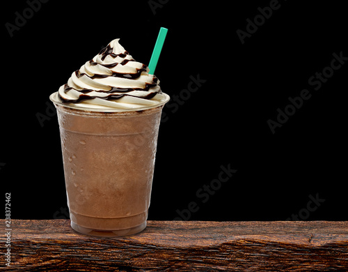 Iced coffee or frappuccino with cream in take away disposable cup mock up or mockup template isolated on wooden table with black background Poster Mural XXL