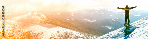 Photo Silhouette of alone tourist standing on snowy mountain top in winner pose with raised hands enjoying view and achievement on bright sunny winter day