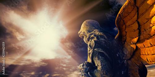 Antique statue of a guardian angel in sunlight. Fototapeta
