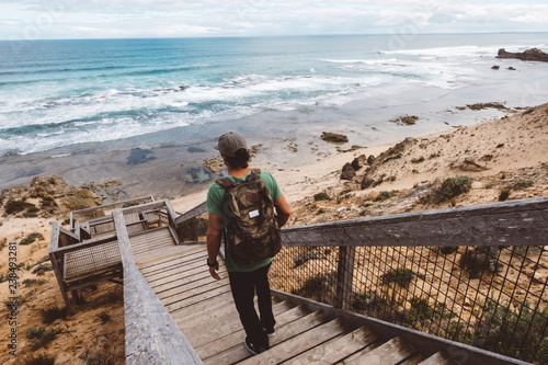 Canvas Print Rear view of hiker with backpack walking down wooden steps at beach