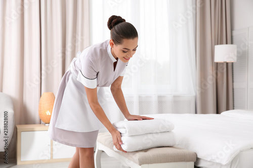 Young chambermaid putting clean towels on bed bench in hotel room