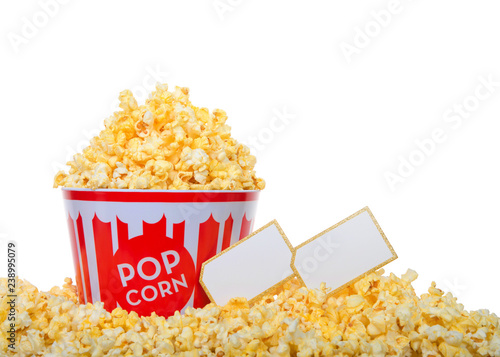 Bucket of pop corn heaped high with popcorn and surrounded by the same, isolated on white background. Two blank movie tickets next to bucket.