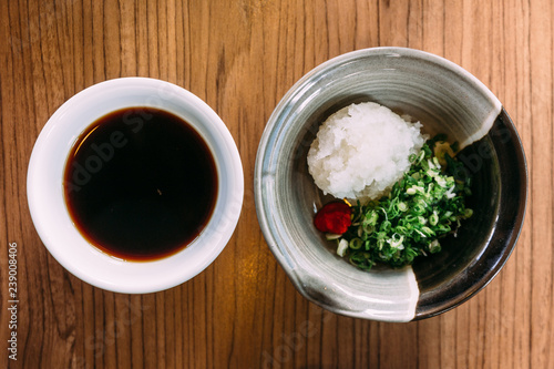 Top view of Shoyu Ponzu (Citrus soy sauce) with minced daikon and scallion.