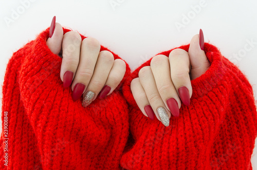 Wallpaper Mural Beautiful female finger nails with red nail close up on red knitted sweater