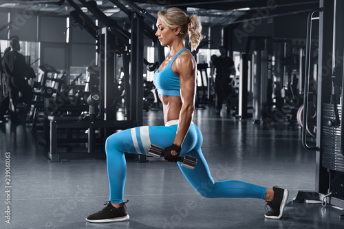 Fotografia Fitness woman doing lunges exercises for leg muscle workout training in gym