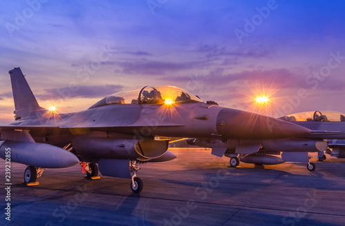 Fotografiet Silhouette fighter jet military aircrafts parked on runway in twilight time with