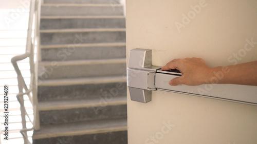 Fotografija Hand is pushing Fire door handle of Fire exit for emergency evacuation